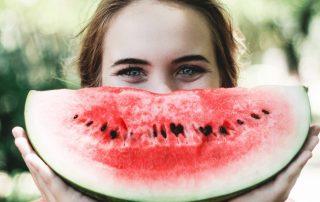 Cardápio saudável. Moça com uma melancia.